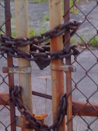 Padlocked parking lot for a former car dealership on Wick Avenue