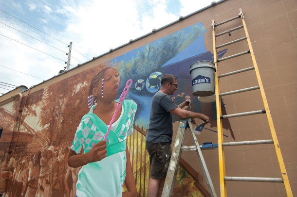 The Youngstown Neighborhood Development Corporation hired Curtis Goldstein, a Columbus-based artist, to paint a mural on the north wall of the former Park Inn on Glenwood Avenue. The earth-toned mural depicts the history of the Idora Park along with portraits of children and residents currently living in the Idora neighborhood. Electronic image by Sean Posey.